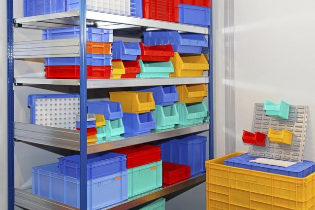 An assortment of plastic bins in different sizes stacked on a shelf.