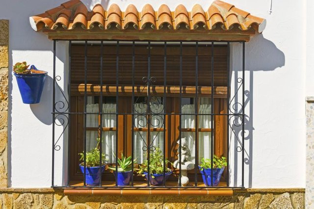 The front of a Spanish style home with blue flower pots