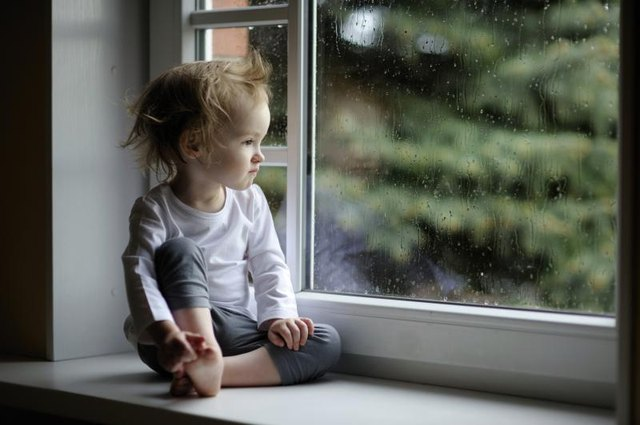 A toddler watching the rain fall from an indoor window.