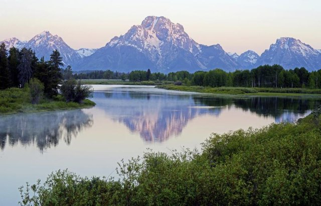 The Tetons are reflected on a stream in Wyoming.
