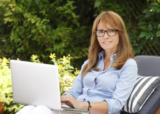 A 40-year-old woman using her laptop on the patio.
