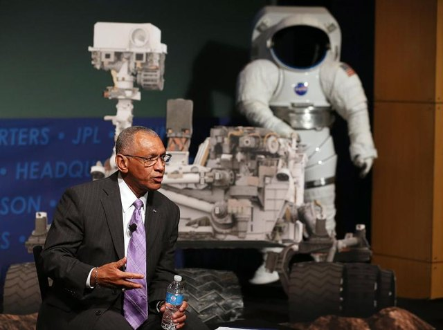 A NASA administrator give a talk in front of a replica of the Curiosity rover and an astronaut suit