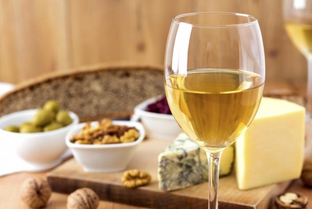 Wine glass with cheese and nuts in background
