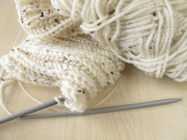 A cream scarf being knitted.