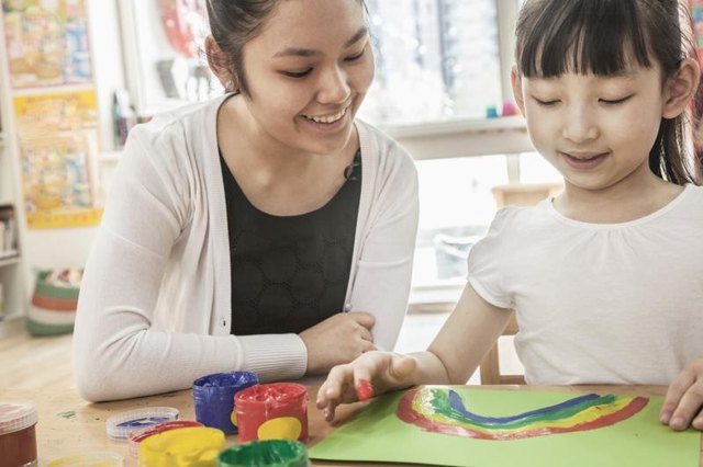 A young woman is helping a little girl with arts and crafts.