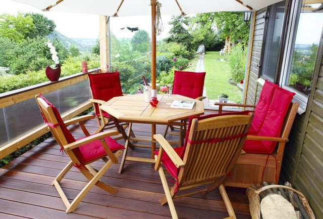 A set of teak patio furniture on the terrace.