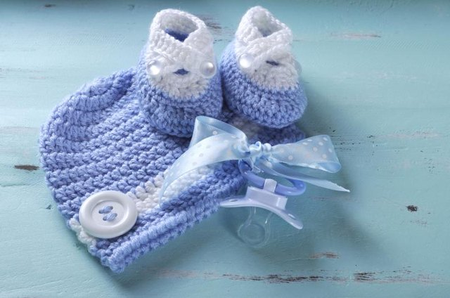 Hand-knitted baby blue hat and booties on a table with a pacifier.