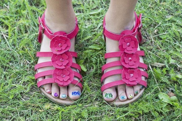 A girl's feet with brightly painted toe nails.