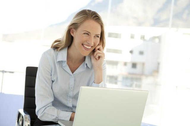 Woman using laptop while on phone