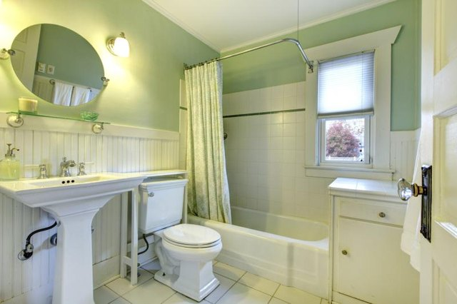White tile, wainscoting and fixtures in a pale green bathroom.