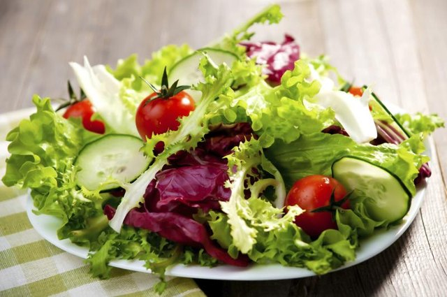 A plate of salad on a wooden table.