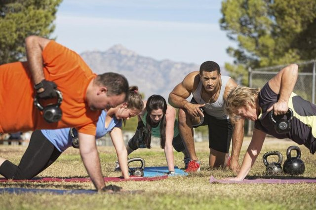 A trainer leads a kettlebell training class.