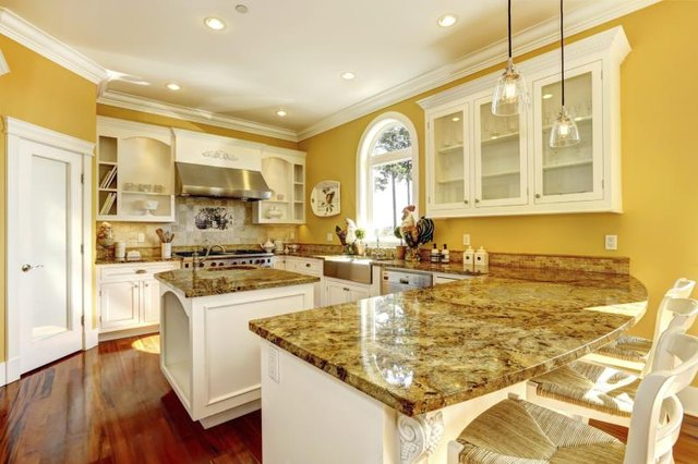 A brightly lit kitchen with several granite countertops