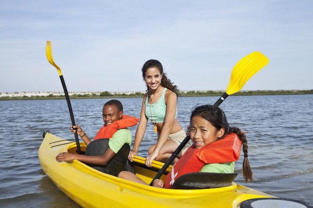 A summer camp counselor is helping young girls learn how to kayak.