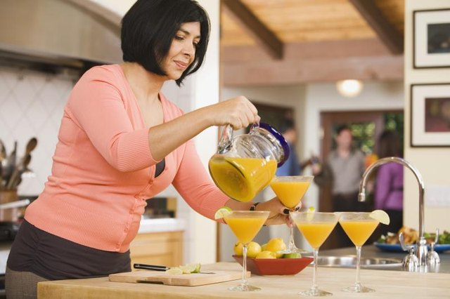 A woman is pouring cocktails.