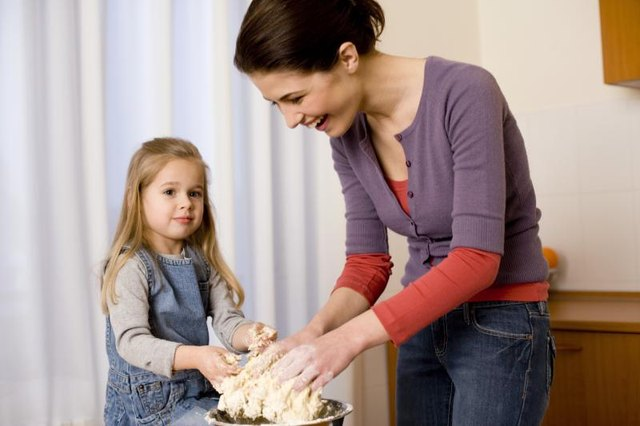 A mother and child make dough together.