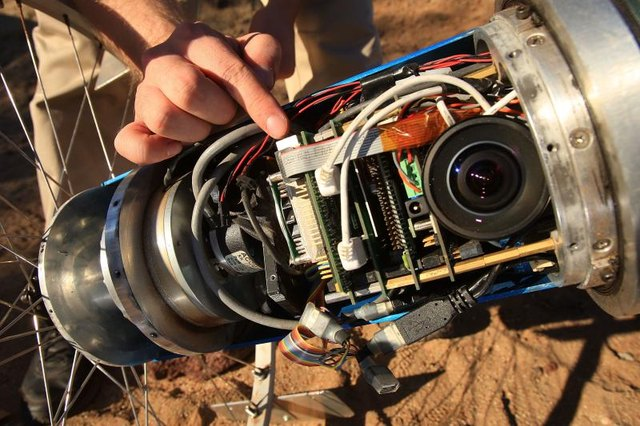 Close-up of an engineer's hand adjusting a camera system designed for a rover