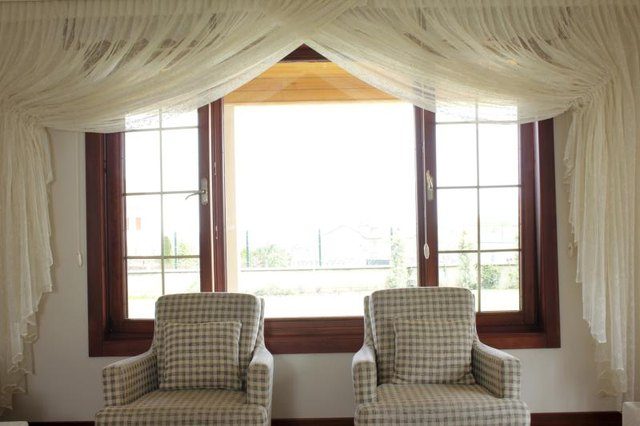 Heavy yet sheer curtains gracing the perimeter of a sitting room window.