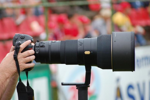 Sports photographer using large zoom lens