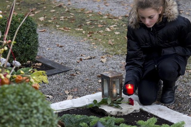 Teenager setting down red candles on sidewalk