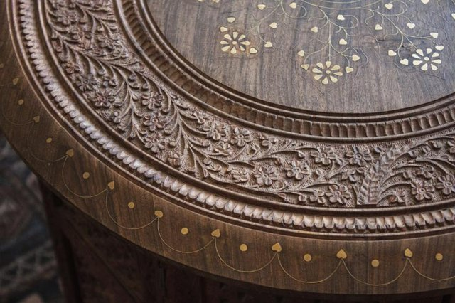 A close-up of a hand carved teak coffeetable.