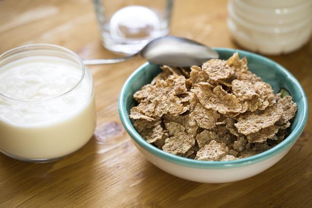 A bowl of wheat-flake cereal on a table with milk and yogurt.