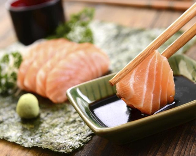A close-up of a person dipping fresh salmon sashimi in soy sauce.