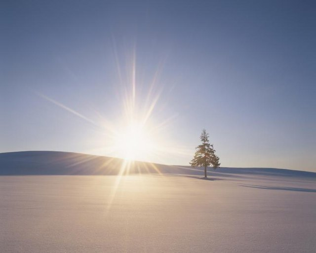 The sun rising over a snowy landscape.