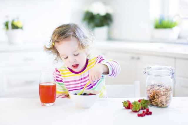 Toddler eating cereal with fruit