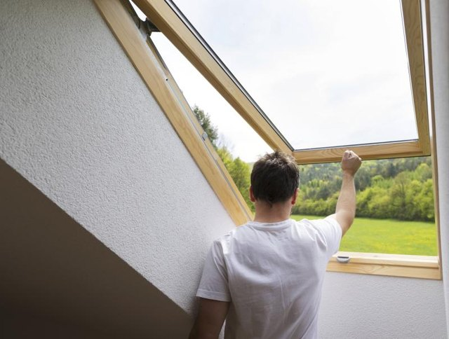 Man opening a skylight in the attic.