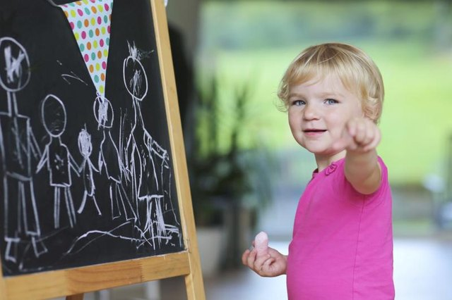 A young child is playing on a chalkboard.