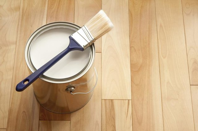 Can of white paint with brush on a wood floor.