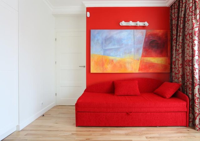 A small bedroom with contemporary art and sofa bed.