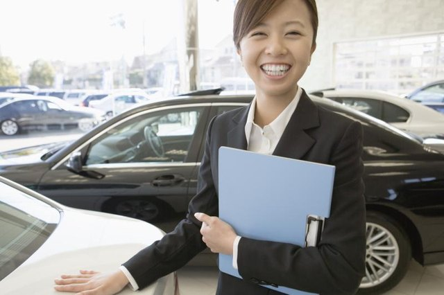 A female sales representative standing the show room of her dealership