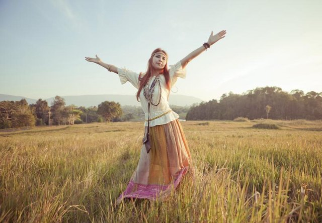 Hippie woman dancing in field