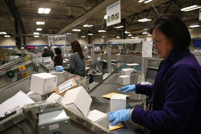 A postal worker sorts through packages at a distribution center