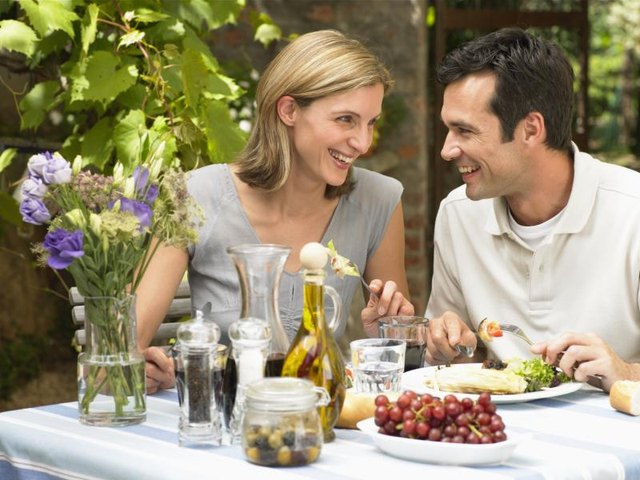 Couple eating lunch at outdoor table with salad on their plates.