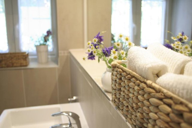 A basket of folded towels in a clutter-free bathroom.