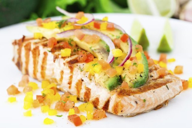 Plate of freshly grilled salmon with avocado salsa on top.
