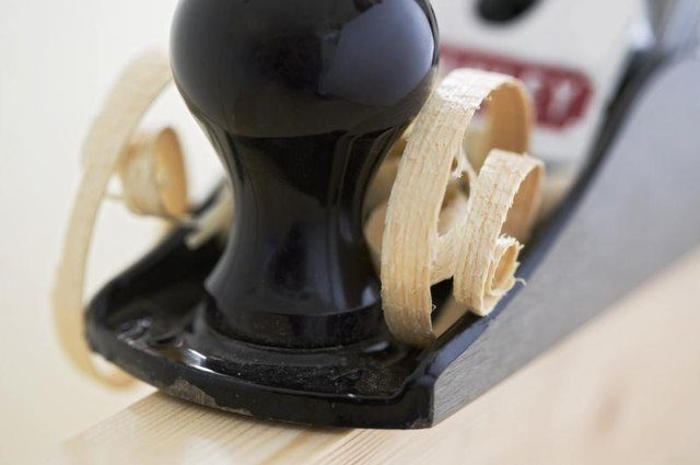 A block plane being used to shave wood.