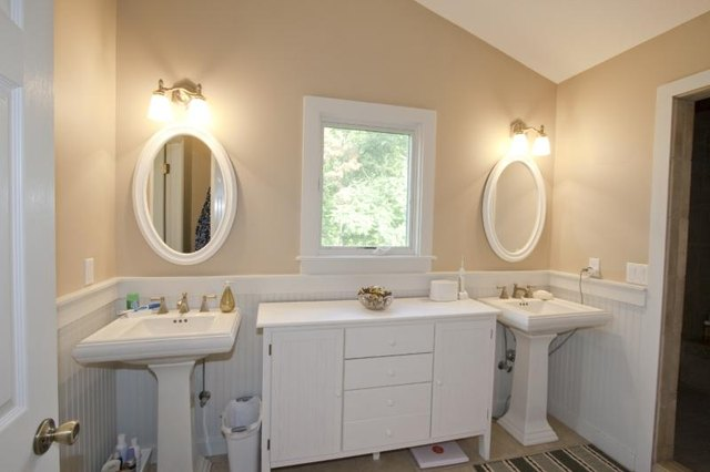 A white cabinet and window between two porcelain pedestal sinks in a bathroom.