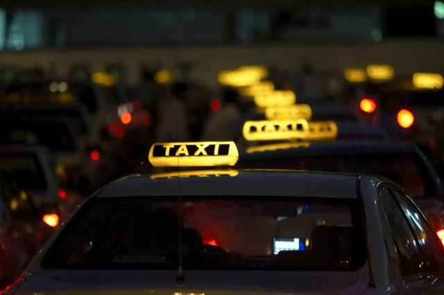 A row of taxis at night.