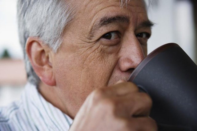 Close-up of man drinking a cup of coffee.