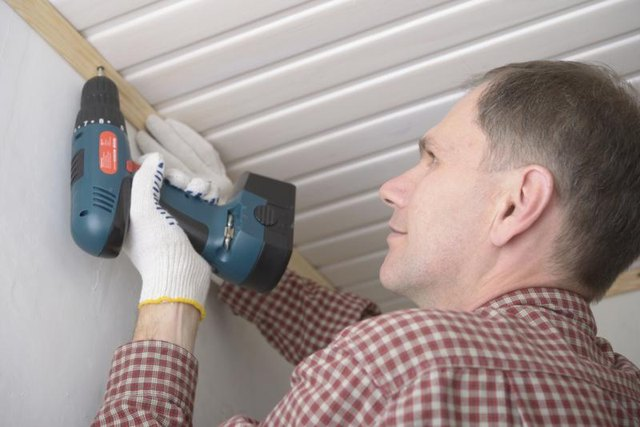 A man is attaching molding to his ceiling using an electric screwdriver.