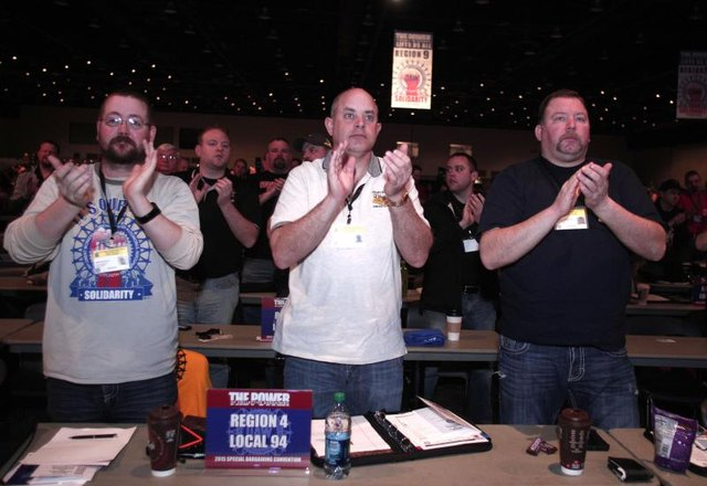 United Auto Worker labor union leaders applauding at a conference.