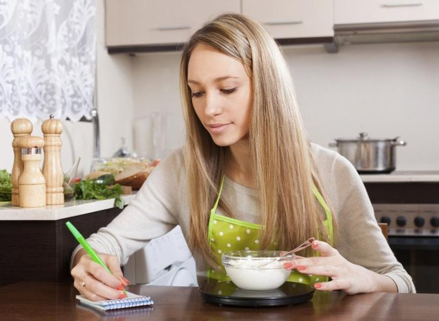 A woman weighs food on a scale while taking notes in her kitchen.