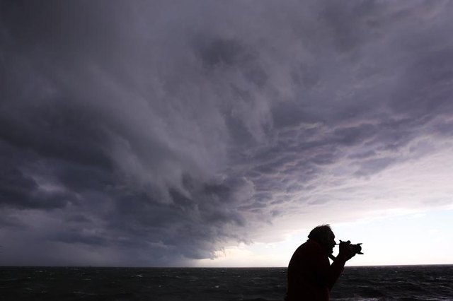 Photographer taking images of storm waves in Australia