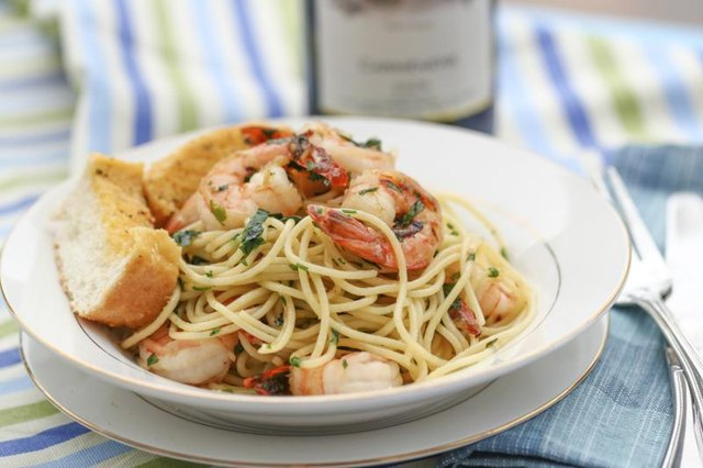 A pasta dish topped with shrimp and garlic bread.