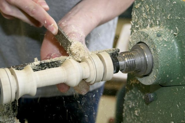 Hands working on a wood lathe.