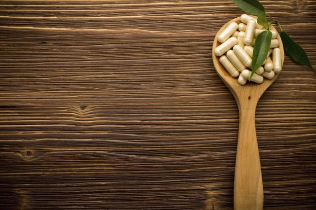Vitamin supplements on wooden spoon.